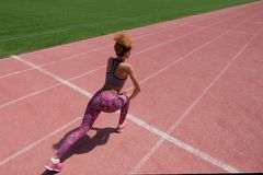 Ασκήσεις στον αθλητικό τομέα Ένα νέο σκοτεινός-ξεφλουδισμένο κορίτσι σε μια γκρίζα μπλούζα, ρόδινα εσώρουχα και πάνινα παπούτσια  στοκ φωτογραφία με δικαίωμα ελεύθερης χρήσης