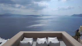 Ασπρισμένες σπίτια και εκκλησία στους απότομους βράχους με την άποψη και Sunbeds θάλασσας Oia, Santorini, Κυκλάδες, Ελλάδα απόθεμα βίντεο