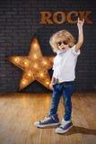 Αστέρας της ροκ μικρών παιδιών που δίνει το βράχο - και - σημάδι ρόλων Στοκ εικόνες με δικαίωμα ελεύθερης χρήσης