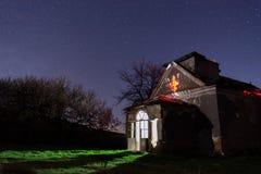 Αστέρια πέρα από μια παλαιά εγκαταλειμμένη αγροτική εκκλησία στοκ φωτογραφία