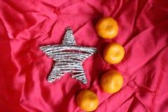 Αστέρι και μανταρίνια στο κόκκινο ύφασμα όπως ένα σύμβολο της σημαίας της Κίνας Στοκ Φωτογραφία