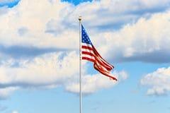 Αστέρι-ριγωτοί κυματισμοί αμερικανικών σημαιών υπερήφανα ενάντια στο μπλε ουρανό Στοκ εικόνα με δικαίωμα ελεύθερης χρήσης