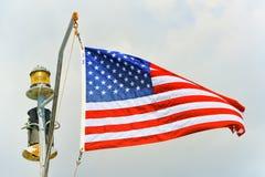 Αστέρι-ριγωτοί κυματισμοί αμερικανικών σημαιών υπερήφανα ενάντια στο μπλε ουρανό Στοκ Εικόνα