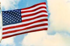 Αστέρι-ριγωτοί κυματισμοί αμερικανικών σημαιών υπερήφανα ενάντια στο μπλε ουρανό Στοκ Φωτογραφία