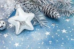 Αστέρι Χριστουγέννων με τη σφαίρα γυαλιού, firtree κλάδος με τον κώνο στο μπλε Στοκ Εικόνα