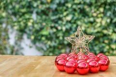 Αστέρι Χριστουγέννων που περιβάλλεται από πολλές κόκκινες σφαίρες Χριστουγέννων, σε ένα ξύλο Στοκ Φωτογραφία