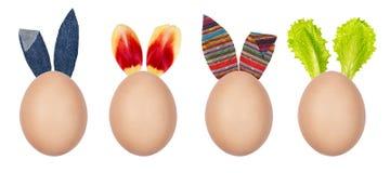 Αστεία αυγά Πάσχας που διακοσμούνται με τα φύλλα σαλάτας, τα πέταλα τουλιπών και τα υφαντικά αυτιά λαγουδάκι Δημιουργική διακόσμη στοκ εικόνα με δικαίωμα ελεύθερης χρήσης