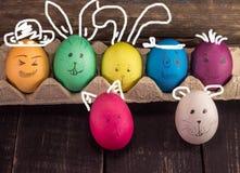Αστεία αυγά Πάσχας στα ξύλινα γραφεία Στοκ φωτογραφία με δικαίωμα ελεύθερης χρήσης