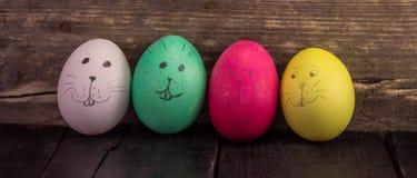 Αστεία αυγά Πάσχας στις αγροτικές ξύλινες σανίδες Στοκ εικόνες με δικαίωμα ελεύθερης χρήσης