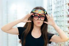 Αστεία γυναίκα που δοκιμάζει πολλά Eyeglasses πλαίσια στο οπτικό κατάστημα Στοκ εικόνα με δικαίωμα ελεύθερης χρήσης