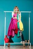 Αστεία γυναίκα που παίρνει όλα τα ενδύματα στη λεωφόρο ή την ντουλάπα Στοκ Φωτογραφίες