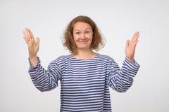 Αστεία γυναίκα στο ριγωτό πουκάμισο που παρουσιάζει κάτι μεγάλο σε μέγεθος με τα χέρια Στοκ Εικόνες