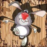 Αστεία διασκέδαση κουνελιών κινούμενων σχεδίων γκρίζα που καλπάζει σε ένα υπόβαθρο του χαρτονιού Στοκ Εικόνες