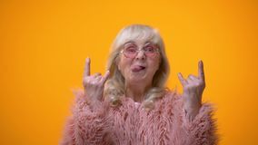 Αστεία ηλικιωμένη γυναίκα στο ρόδινο παλτό που κάνει rocker τις χειρονομίες και που παρουσιάζει γλώσσα, διασκέδαση απόθεμα βίντεο