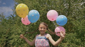 Αστεία ιδέα με τα μπαλόνια Το εύθυμο και όμορφο κορίτσι με τις ζωηρόχρωμες σφαίρες συνδέθηκε με την τρίχα και τις πλεξούδες της σ φιλμ μικρού μήκους