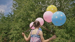 Αστεία ιδέα με τα μπαλόνια Το εύθυμο και όμορφο κορίτσι με τις ζωηρόχρωμες σφαίρες συνδέθηκε με την τρίχα και τις πλεξούδες της σ απόθεμα βίντεο