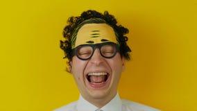 Αστεία και χαρωπά ανθρώπινη συγκίνηση πορτρέτου του νέου σγουρού γελώντας ατόμου, στο κίτρινο υπόβαθρο τοίχων απόθεμα βίντεο