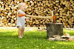 Αστεία κοπή μικρών παιδιών firewoods με ένα τεράστιο τσεκούρι Στοκ εικόνες με δικαίωμα ελεύθερης χρήσης