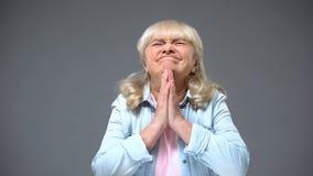 Αστεία κυρία συνταξιούχων που κάνει την επιθυμία που αναμένει τις καλές ειδήσεις, που περιμένουν τα παιδιά τις διακοπές στοκ φωτογραφία