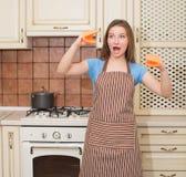 Αστεία μαγειρεύοντας γυναίκα ψησίματος που έχει τη διασκέδαση στην κουζίνα της που χαμογελά che Στοκ Φωτογραφίες