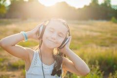 Αστεία μουσική ακούσματος κοριτσιών με τα ακουστικά Στοκ εικόνα με δικαίωμα ελεύθερης χρήσης
