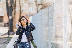 αστεία μουσική ακούσματος κοριτσιών στα ακουστικά στην οδό Στοκ Φωτογραφία