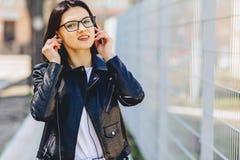 αστεία μουσική ακούσματος κοριτσιών στα ακουστικά στην οδό Στοκ εικόνα με δικαίωμα ελεύθερης χρήσης