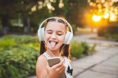 Αστεία μουσική ακούσματος κοριτσιών στο τηλέφωνο Στοκ εικόνα με δικαίωμα ελεύθερης χρήσης