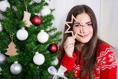 Αστεία νέα γυναίκα με το διακοσμημένο χριστουγεννιάτικο δέντρο Στοκ Εικόνες