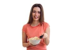 Αστεία νέα γυναίκα που προσέχει τη TV με pop-corn Στοκ Φωτογραφίες