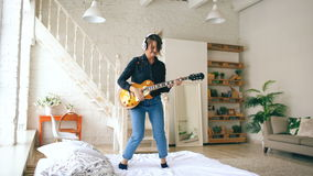 Αστεία νέα γυναίκα στα ακουστικά που πηδά στο κρεβάτι με την ηλεκτρική κιθάρα στην κρεβατοκάμαρα στο σπίτι στο εσωτερικό απόθεμα βίντεο