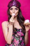 Αστεία νέα γυναίκα στη μάσκα ύπνου και πυτζάμες, γλυκά στο ρόδινο υπόβαθρο Πρόσωπο ομορφιάς στοκ εικόνες με δικαίωμα ελεύθερης χρήσης