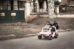 Αστεία παιδιά που παίζουν με ένα σκουριασμένο αυτοκίνητο παιχνιδιών σε μια φτωχή οδό στη Μαδαγασκάρη Στοκ εικόνες με δικαίωμα ελεύθερης χρήσης