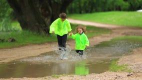 Αστεία παιδιά που τρέχουν μέσω της τεράστιας λίμνης στο πράσινο πάρκο