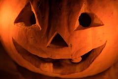 Αστεία πορτοκαλιά κολοκύθα όπως ένα κεφάλι με τα μάτια και ένα χαμόγελο σε ένα blac Στοκ φωτογραφία με δικαίωμα ελεύθερης χρήσης