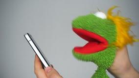 Αστεία πράσινη μαριονέτα που κοιτάζει βιαστικά στο smartphone φιλμ μικρού μήκους