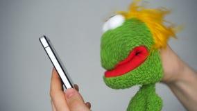 Αστεία πράσινη μαριονέτα που κοιτάζει στο smartphone απόθεμα βίντεο