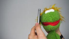 Αστεία πράσινη μαριονέτα που μιλά από το smartphone φιλμ μικρού μήκους