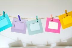 Αστεία πλαίσια εικόνων Colorfu που κρεμούν στο σχοινί με το σπάγγο clothespins στοκ εικόνες