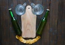 Αστεία ρύθμιση των τσιπ, κούπες μπύρας, μπουκάλια της μπύρας και ενός ξύλινου πίνακα για τα πρόχειρα φαγητά, σε έναν ξύλινο καφετ Στοκ Εικόνες