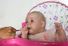 Αστεία σίτιση μωρών με ένα κουτάλι στοκ φωτογραφίες