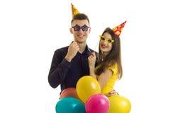 Αστεία συμπαθητικά γυαλιά εγγράφου εκμετάλλευσης τύπων και κοριτσιών πολλά χρωματισμένα μπαλόνια και χαμόγελο στοκ εικόνες