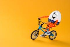 Αστεία συνεδρίαση αυγών Πάσχας σε ένα μικροσκοπικό ποδήλατο στοκ εικόνες