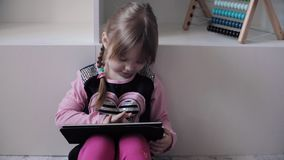 Αστεία συνεδρίαση παιδιών στο πάτωμα και χρησιμοποίηση των ηλεκτρονικών συσκευών απόθεμα βίντεο