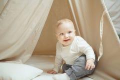 Αστεία συνεδρίαση παιδιών χαμόγελου στη σκηνή με το μαξιλάρι, λίγο μικρό παιδί Στοκ Φωτογραφίες