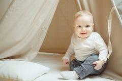 Αστεία συνεδρίαση παιδιών χαμόγελου inwigwam με το μαξιλάρι, λίγο μικρό παιδί Στοκ Εικόνα