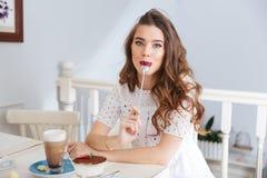 Αστεία συνεδρίαση γυναικών στον καφέ με το κουτάλι στο στόμα της στοκ φωτογραφίες