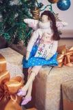 Αστεία συνεδρίαση κοριτσιών αγγέλου tilda στα νέα δώρα έτους Στοκ φωτογραφία με δικαίωμα ελεύθερης χρήσης