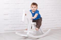 Αστεία συνεδρίαση μωρών στο άλογο παιχνιδιών στοκ φωτογραφίες