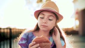 Αστεία τρία έτη κοριτσιών, που τρώνε ένα χάμπουργκερ στον ήλιο απόθεμα βίντεο